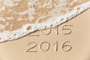 2015 2016 inscription written in the wet yellow beach sand being